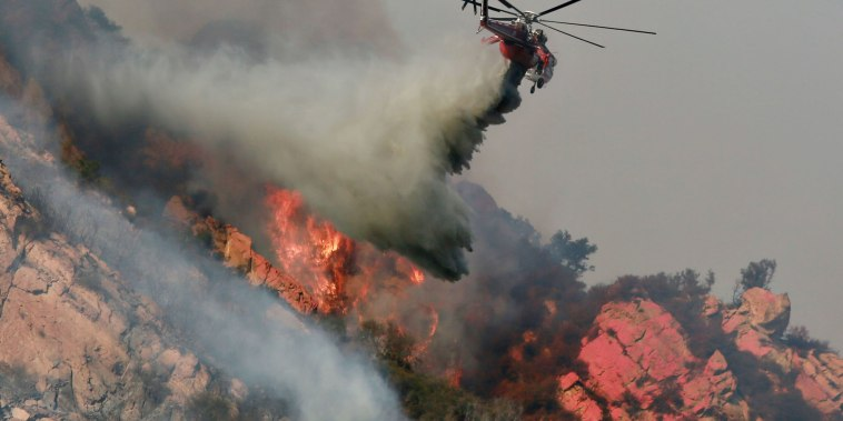 Image: A helicopter drops flame retardant on a wildfire on Nov. 10, 2018 in Malibu, California.