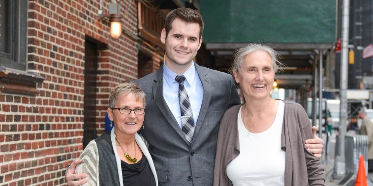 Zach Wahls poses for a photo with his moms, Jacqueline Reger, left, and Terry Wahls, right, in New York in 2012.