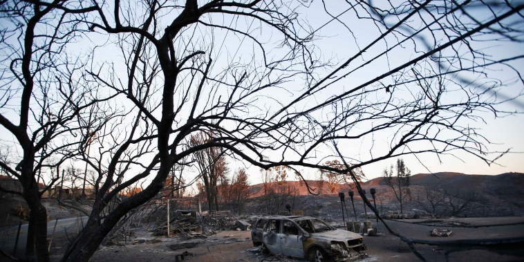 Image: The burnt wreckage of a vehicle and debris are seen in the aftermath of the Woolsey fire in Malibu, Southern California
