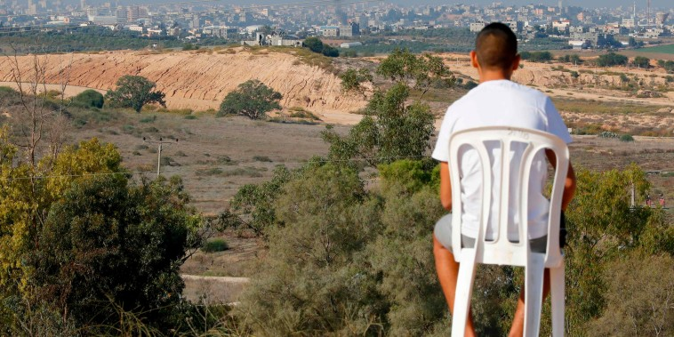 Image: An Israeli man looks at smoke billowing from the other side on a hill overlooking Israel's border with the Gaza Strip in the southern city of Sderot