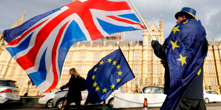 Image: An anti-Brexit demonstrator waves a Union flag alongside a European Union flag outside the Houses of Parliament in London