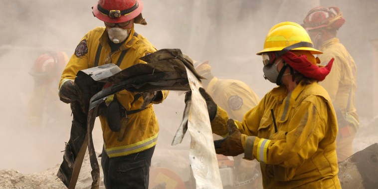 Image: Cal Fire firefighters comb through a house destroyed by the Camp Fire in Paradise