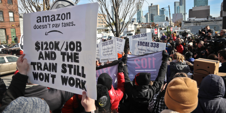 Protesters carry signs during a rally and press conference opposing the Amazon headquarters in Long Island City, New York, on Nov. 14, 2018.