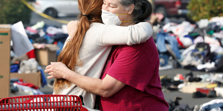 Maddy Mudd, 25, of Oakhurst, hugs Camp Fire evacuee Terri Wolfe, 62, of Paradise, at a donation site for evacuees in Chico