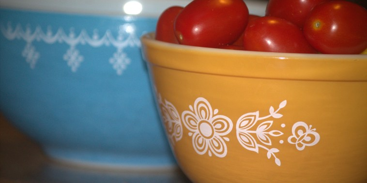 Two vintage Pyrex bowls, one blue and one orange. The orange contains bright red grape tomatoes.