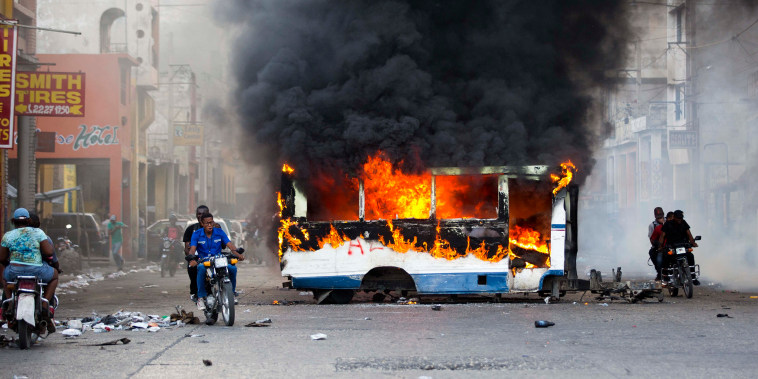 Image: Motorcyclists pass a burning bus set on fire by protesters in Port-au-Prince