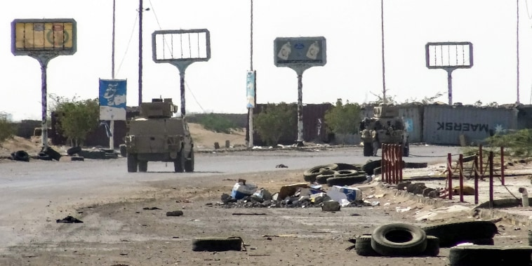 Image: Armoured vehicles of the Yemeni pro-government forces are seen driving past destruction in an industrial district in the eastern outskirts of the port city of Hodeida