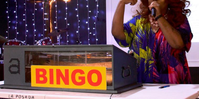 Joe Uvalles, a.k.a. Beatrix Lestrange, pulls a bingo number at the migrant charity event.