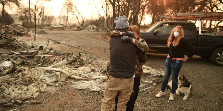Image: Kimberly Spainhower hugs her husband Ryan Spainhower while their daughter Chloe Spainhower, 13, looks on at the burned remains of their home in Paradise, California on Nov. 18, 2018.