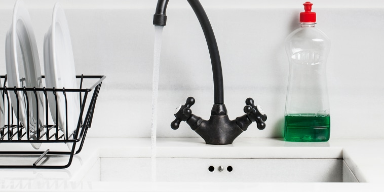 A sink, water tap and dish soap in a kitchen.