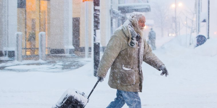 Image: A man moves luggage in snow during a winter storm in Buffalo, NY