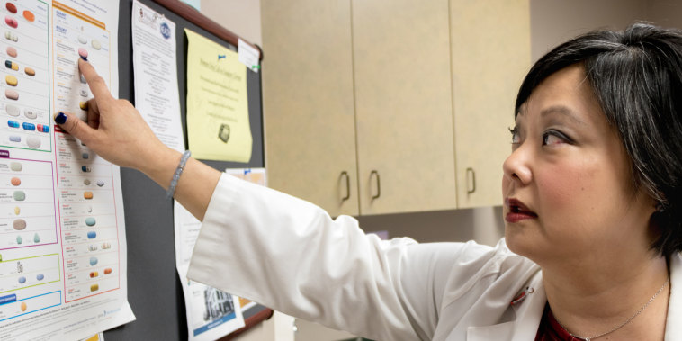 Dr. Michelle Salvaggio, medical director of the Infectious Diseases Institute at the University of Oklahoma Health Sciences Center in Oklahoma City, points to drugs used to treat HIV/AIDS. Medical advancements since the epidemic surfaced in the 1980s have helped many of her HIV-positive patients lead healthy lives.