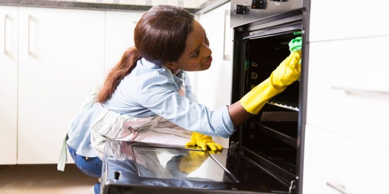 Woman cleaning stove.