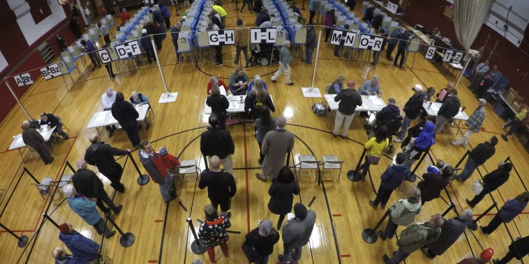 Voters wait in line in the gymnasium at Brunswick Junior High School to receive their ballots for the mid-term election, in Brunswick, Maine, on Nov. 6, 2018.