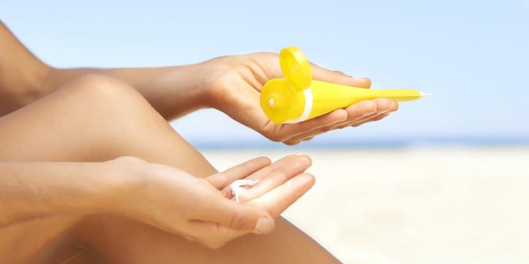 Image: Woman applying sun cream to legs