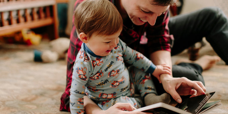 Happy father showing picture book to son while sitting on carpet at home