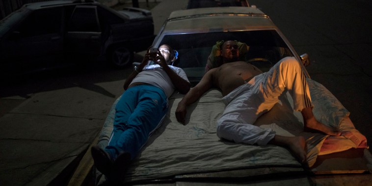 Image: Andres Quintero, left, and Fermin Perez rest on top of Perez's car as they wait in line for over 20 hours to fill their tanks with gas in Cabimas, Venezuela