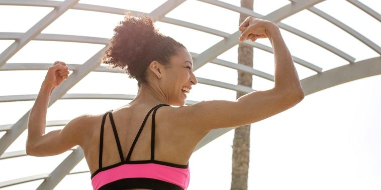 Mixed Race woman flexing arms