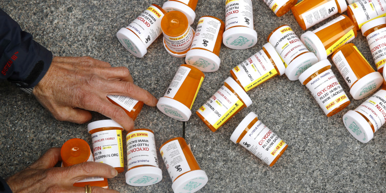 A protester gathers containers depicting OxyContin prescription pill bottles after a demonstration against the FDA's opioid prescription drug approval practices on April 5, 2019, in front of the Department of Health and Human Services' headquarters in Washington.