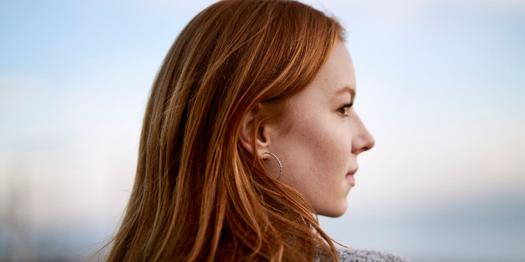 Close up of intense red hair of teenager looking out to sea on a beach in winter