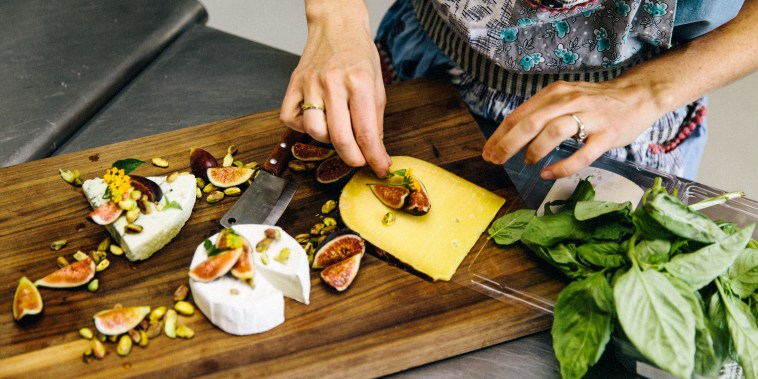 Woman preparing variety cheese plate with figs, nuts, pistachios, basil on wooden chopping board