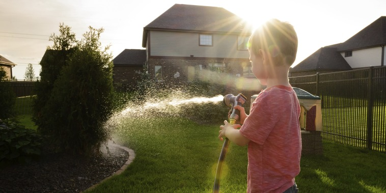 Boy watering plants while standing in yard