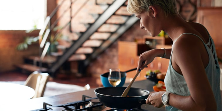 Image: Young woman cooking in loft apartment