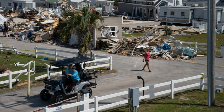 A woman walks past destroyed homes at the Boardwalk RV Park in Emerald Isle, North Carolina on Sept.7 2019, days after a tornado caused by Hurricane Dorian touched down. There are 60 homes in the park but many were destroyed beyond recognition.