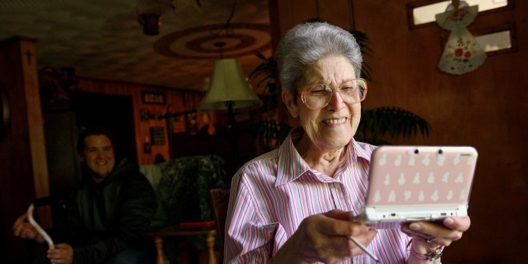 "Image: Audrey Buchanan, 88, plays ""Animal Crossing"" on her pink Nintendo 3DS XL in her living room at her home in Berlin"