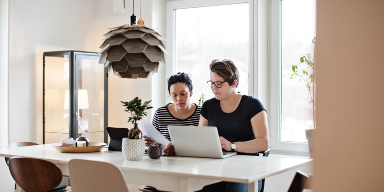Image: Lesbian couple discussing financial bills over laptop while sitting at table