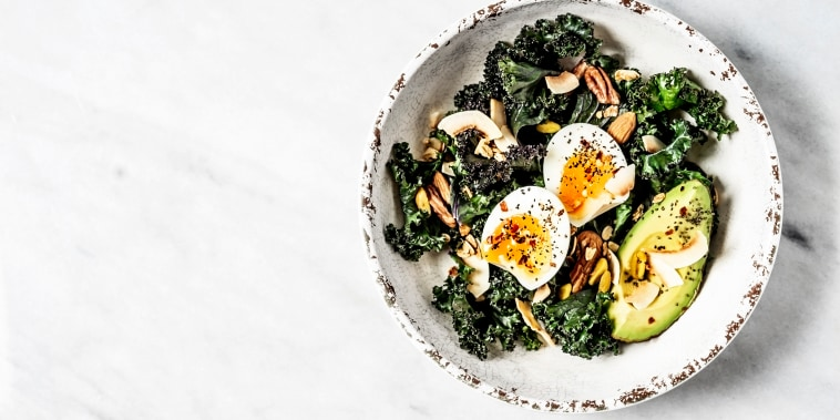 Image: Bowl of kale salad with boiled eggs and avocado on white background