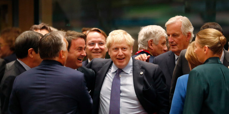 Image: British Prime Minister Boris Johnson, center, is greeted by Luxembourg's Prime Minister Xavier Bettel, center left, during a round table meeting at an EU summit in Brussels