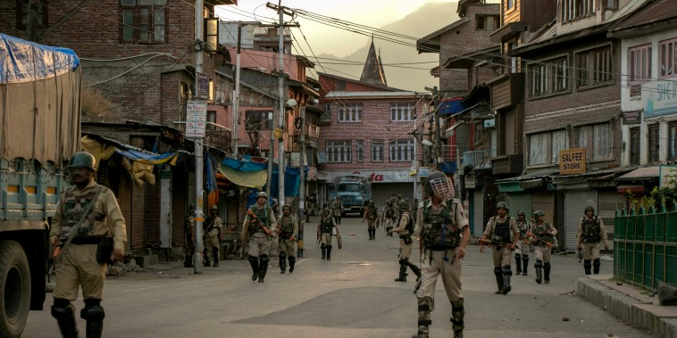 Image: Indian security personnel walk on a street in Srinagar on Aug. 9, 2019.