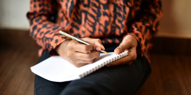 Image: Woman writing on Notepad