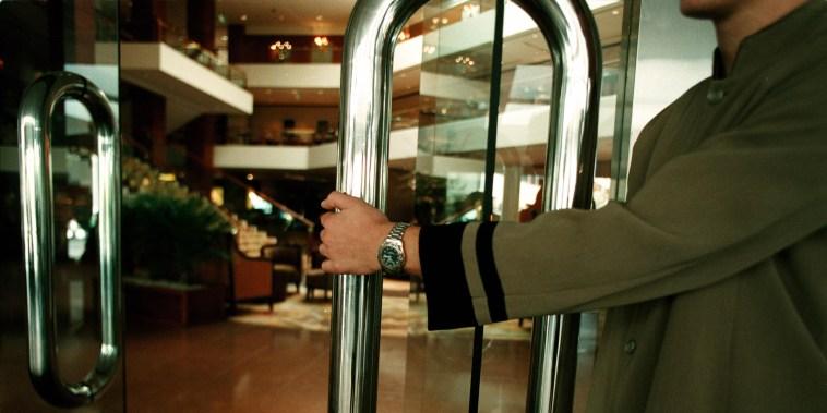Image: A doorman opening the door to a luxury hotel foyer, 25 June 2002