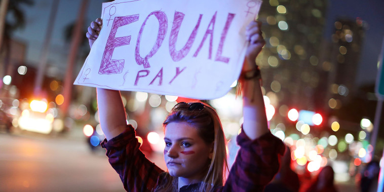"Image: A woman holds a sign that reads, ""Equal Pay"" during ""A Day Without A Woman"" demonstration in Miami"