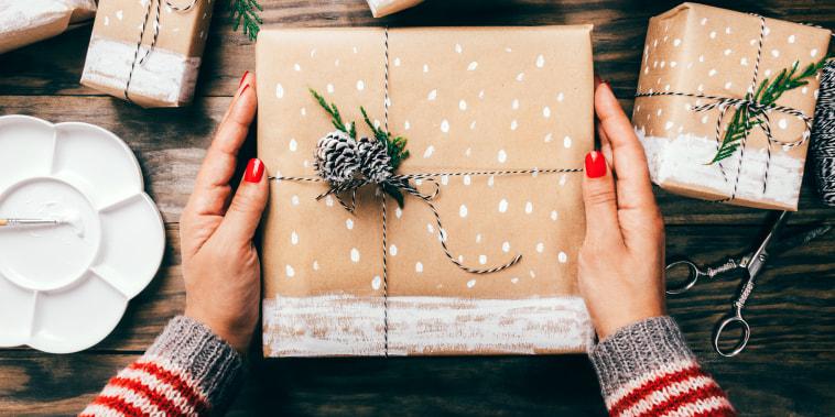 High Angle View Of Woman Holding Christmas Present On Table