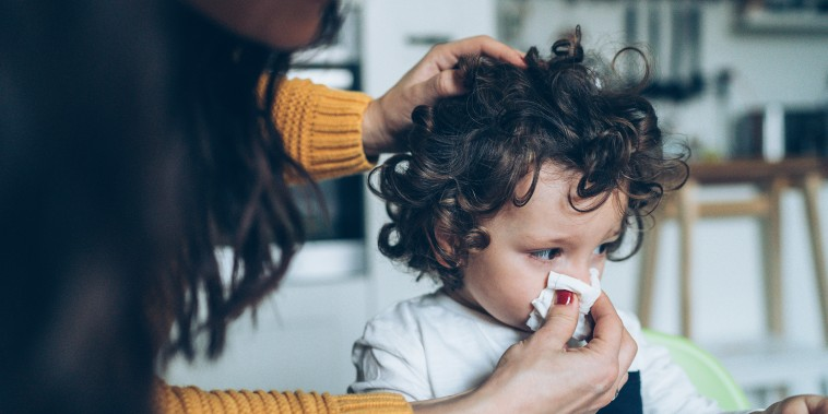 Mother helping son to blow his nose