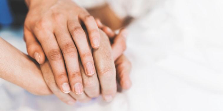 Cropped image of nurse holding man's hand