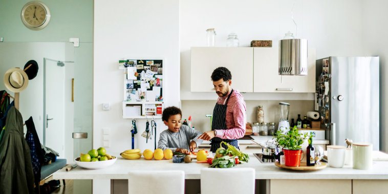 Father And Son Helping Each Other Prepare Some Lunch
