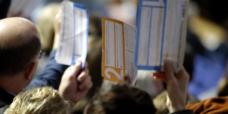 Image: Caucus goers hold up their first votes as they are counted in Des Moines, Iowa