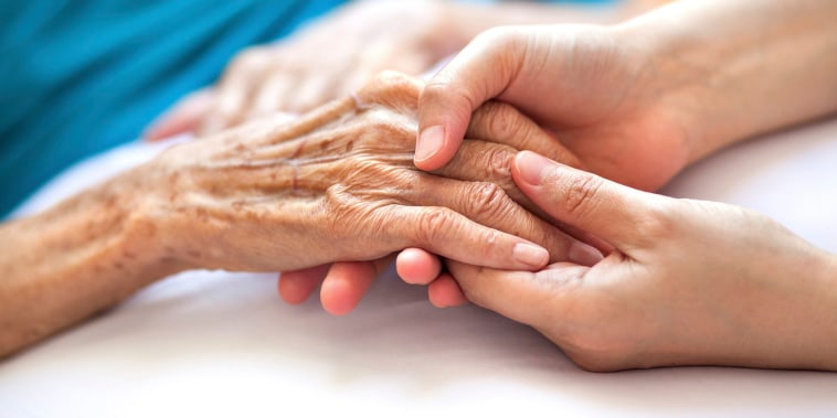 Image: Woman holding senior woman's hand on bed
