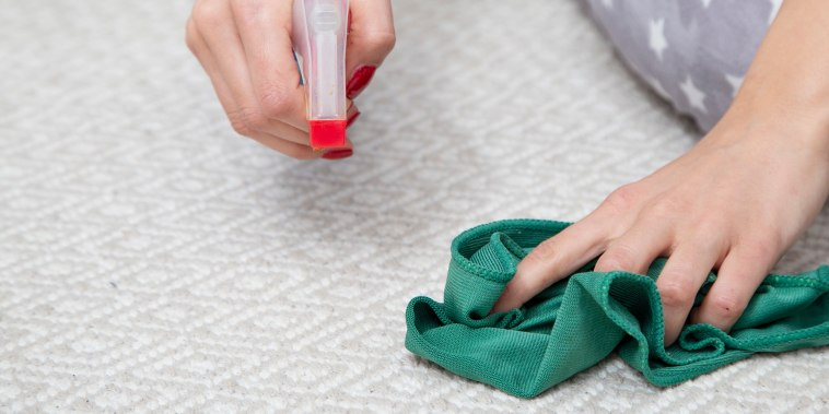 Cleaning carpet with green cloth and spray, close up