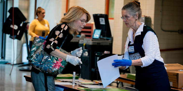 Image: An election worker assists a voter during the Florida primary in Miami