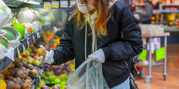 Pandemic times shopping. A young woman wearing a protective mask and gloves buying food supplies, picking fruits in a supermarket.
