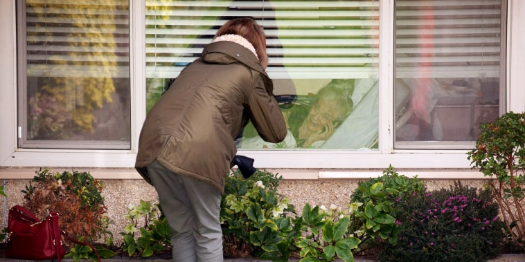 Image: Lori Spencer speaks to her mother, Judie Shape, through a window at the Life Care Center of Kirkland in Washington on March 8, 2020. The assisted living facility is linked to several confirmed coronavirus cases in the state.