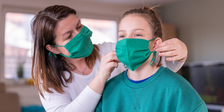 Mother wearing a homemade protective mask and putting one to her daughter