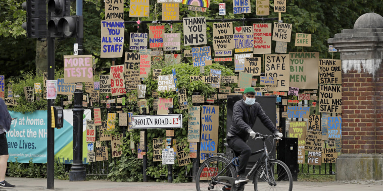 A cyclist passes signs supporting the National Health Service in a display coordinated by artist and local resident Peter Liversidge in east London, on April 27, 2020.