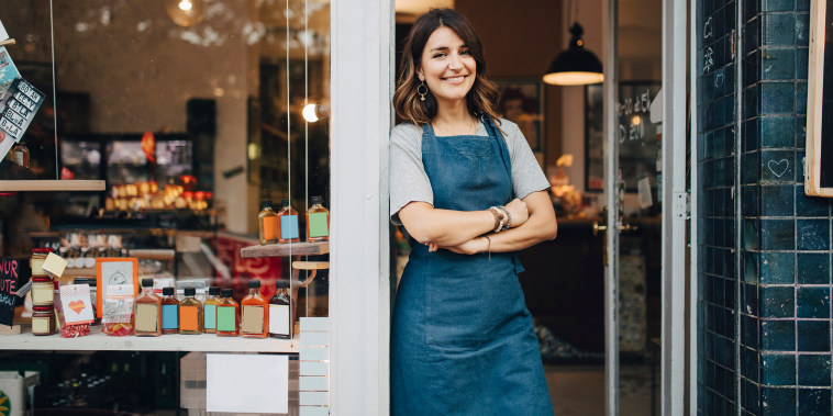 Portrait of confident female owner standing at entrance of deli