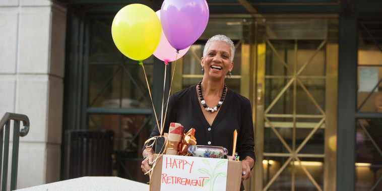Black woman carrying belongings with happy retirement sign and balloons